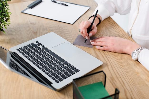 Giovane scrittura della donna di affari sulla nota con la penna sopra lo scrittorio di legno con il computer portatile