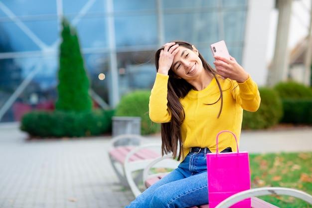 Giovane seduta della donna del brunette all'aperto sul banco con i sacchetti di acquisto dentellare e fare i selfie. donna vestita in maglione giallo
