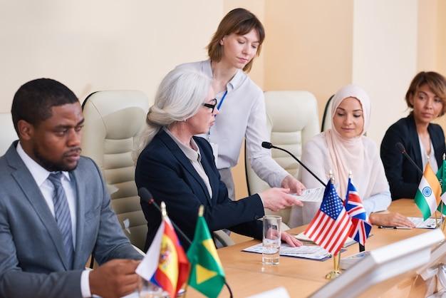 Giovane segretaria che consegna documenti a uno dei delegati interculturali alla conferenza prima del suo discorso