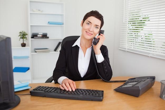 Giovane segretaria che risponde al telefono