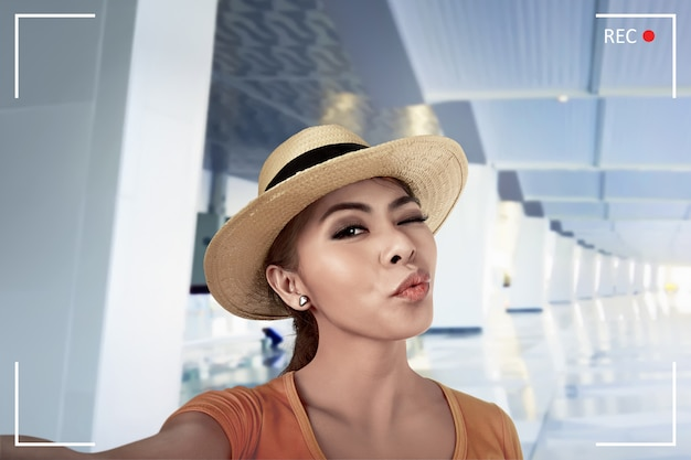Giovane selfie asiatico di posa della donna nella lobby dell'aeroporto