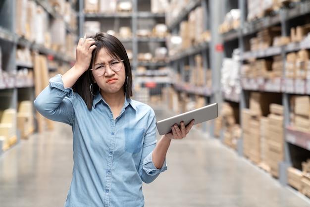 Giovane sensazione asiatica infelice della donna confusa nel magazzino.