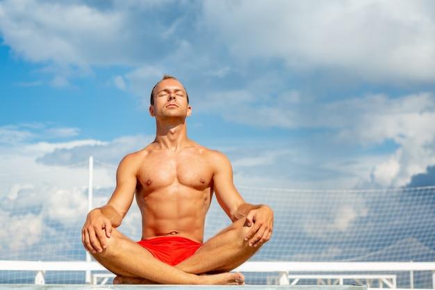 Giovane senza camicia bello durante la meditazione o facendo un esercizio di yoga all'aperto seduto contro il cielo blu.