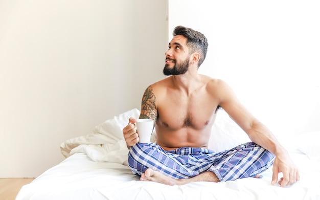Giovane senza camicia che si siede sul letto che tiene tazza di caffè