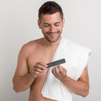 Giovane senza camicia felice con l'asciugamano che lucida il suo unghia usando bene