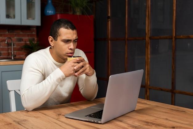 Giovane serio che esamina un computer portatile