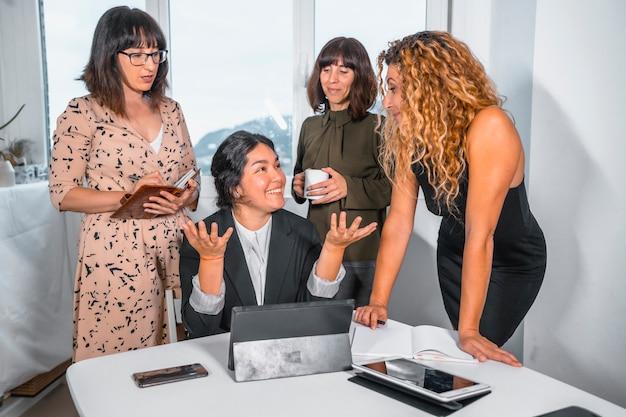 Giovane sessione imprenditoriale in ufficio, capo di un gruppo etnico latino seduto e tre giovani donne caucasiche in piedi accanto a lei al tavolo