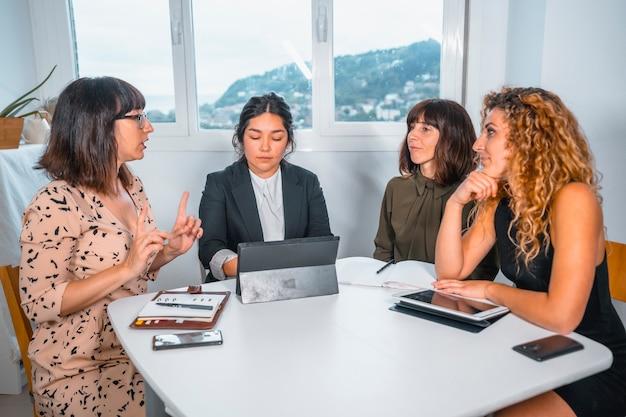 Giovane sessione imprenditoriale in ufficio, un giovane latinoamericano e tre giovani donne caucasiche in una riunione di lavoro al tavolo