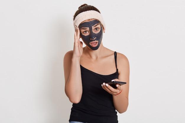 Giovane signora affascinante con la maschera cosmetica facciale nera tramite cellulare, tenendo il dito vicino al tempio, avendo un'espressione del viso stupita e perplessa.