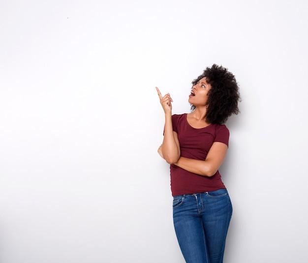 Giovane signora africana sorpresa che osserva in su e che indica sulla priorità bassa bianca