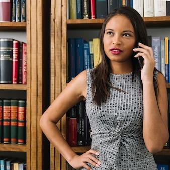 Giovane signora afroamericana pensierosa che parla sullo smartphone vicino ai libri
