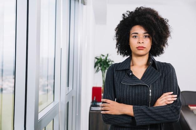 Giovane signora afroamericana seria vicino alla finestra