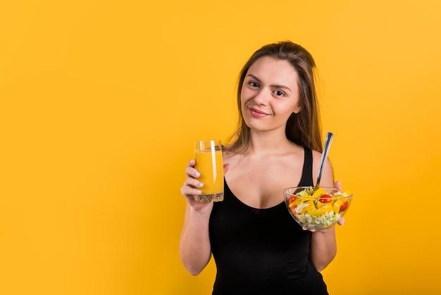 Giovane signora allegra con bicchiere di succo e ciotola di insalata