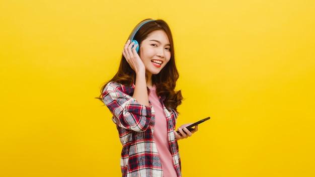 Giovane signora asiatica che indossa le cuffie senza fili che ascolta la musica dallo smartphone con espressione allegra in abbigliamento casual e che esamina macchina fotografica sopra la parete gialla. concetto di espressione facciale.