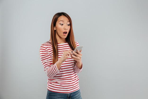 Giovane signora asiatica colpita che chiacchiera dal telefono