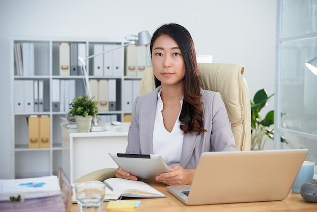 Giovane signora asiatica di affari che posa nell'ufficio con la compressa davanti al computer portatile