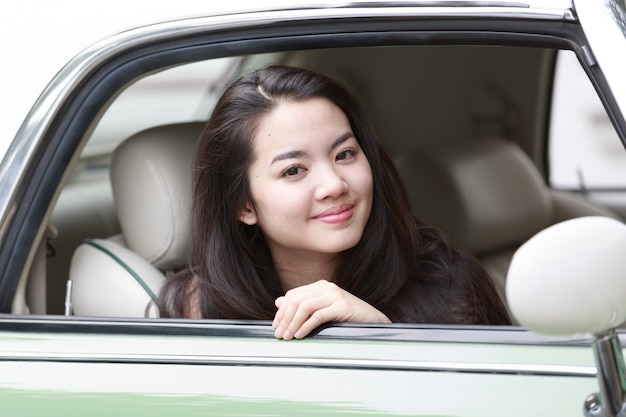 Giovane signora asiatica in un'auto d'epoca