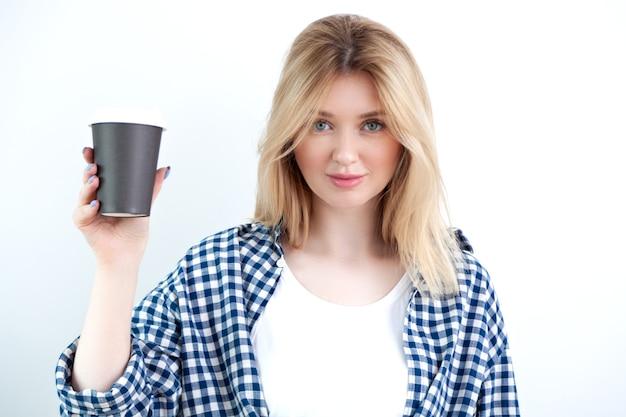 Giovane signora bionda in camicia a scacchi casuale che tiene tazza di caffè nero usa e getta