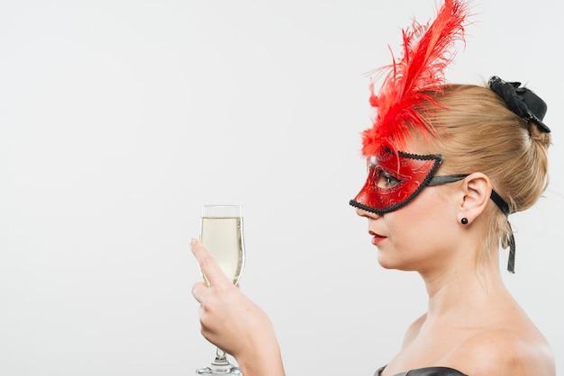 Giovane signora bionda in maschera con le piume rosse che tiene vetro