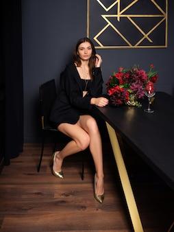 Giovane signora carina e scura in minigonna e giacca, è seduta dietro un lungo tavolo vicino al vaso con fiori