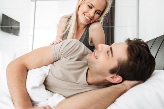 Giovane signora che esamina suo marito mentre trovandosi a letto