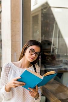 Giovane signora che guarda l'obbiettivo e tenendo il libro vicino alla finestra