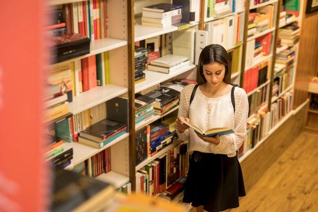 Giovane signora che legge vicino a scaffale per libri