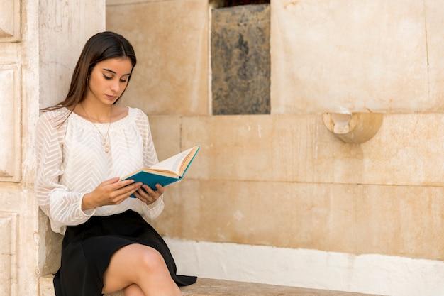 Giovane signora che si siede e libro di lettura vicino alla costruzione di pietra