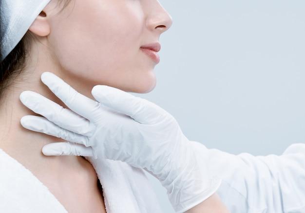 Giovane signora con pelle pulita che osserva in avanti in clinica