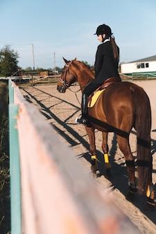 Giovane signora concentrata che si siede sul suo cavallo.