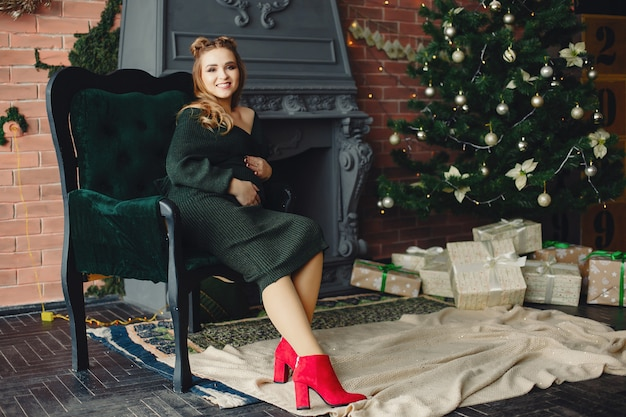 Giovane signora elegante che si siede vicino all'albero di natale