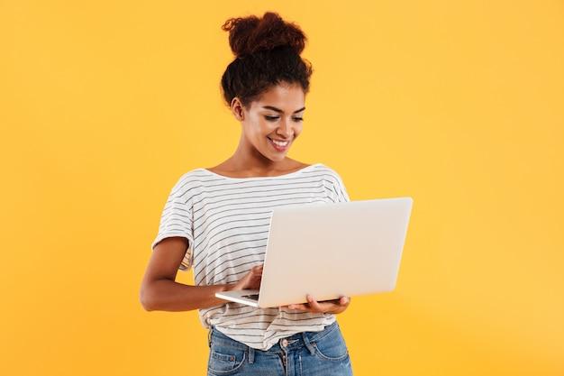 Giovane signora fresca positiva con capelli ricci facendo uso del computer portatile isolato