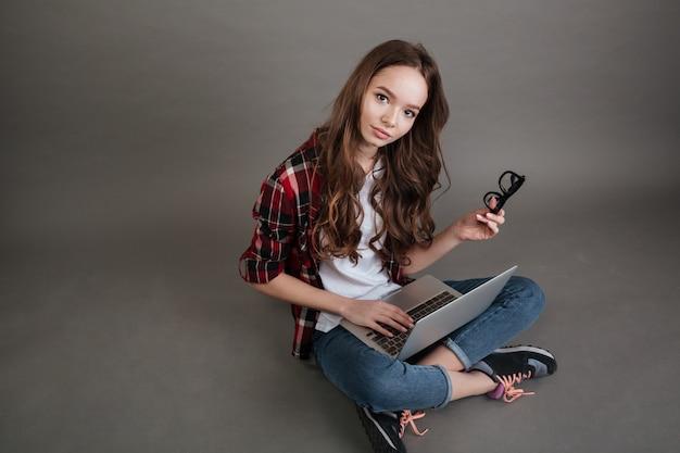 Giovane signora graziosa che chiacchiera dal computer portatile