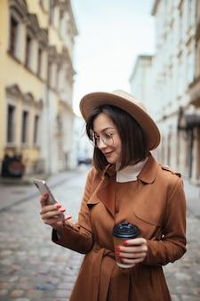 Giovane signora graziosa che parla sul telefono cellulare che cammina all'aperto nel giorno freddo di autunno