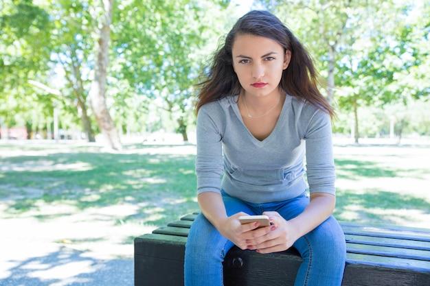 Giovane signora graziosa seria che utilizza smartphone sul banco nel parco