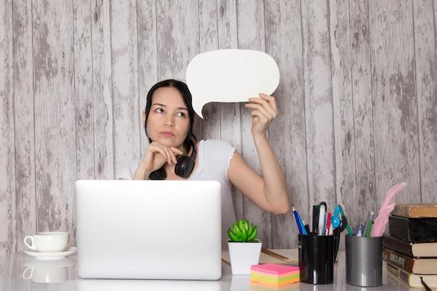 Giovane signora in maglietta bianca auricolari neri pensando di tenere il cartello bianco con laptop grigio sul tavolo tazza di caffè pianta penne libri su grigio