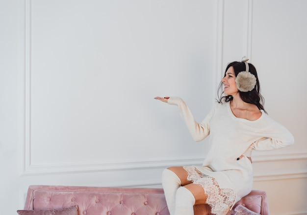 Giovane signora in vestito bianco che posa nella sala
