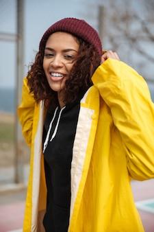 Giovane signora riccia africana felice che porta cappotto giallo che cammina all'aperto