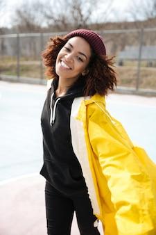 Giovane signora riccia africana felice che porta cappotto giallo