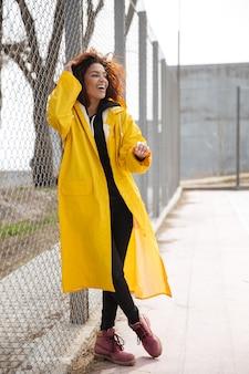 Giovane signora riccia africana stupefacente che porta cappotto giallo