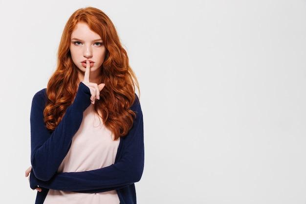 Giovane signora seria di redhead che mostra gesto di silenzio.