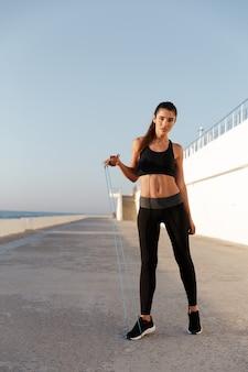 Giovane signora sicura di forma fisica che si prepara vicino al mare