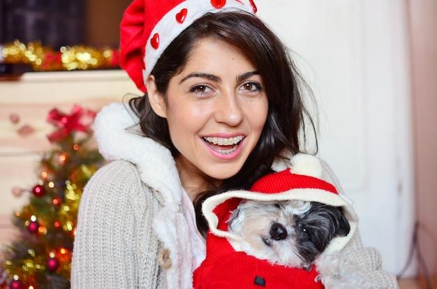 Giovane signora sorridente con il suo cane indossando costume della santa