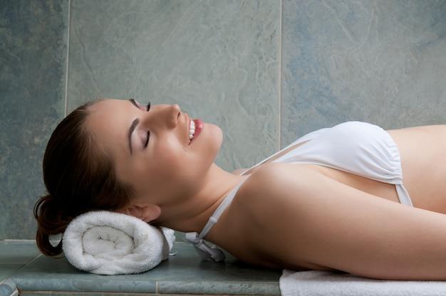 Giovane signora sorridente felice che si rilassa in un bagno turco al centro termale