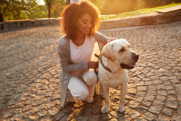 Giovane signora sorridente in abbigliamento casual che si siede e che abbraccia cane nel parco