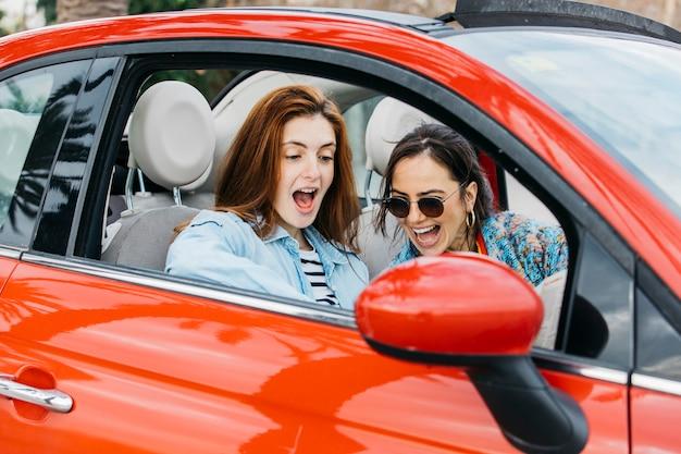 Giovane signora stupita e donna allegra che si siedono in automobile