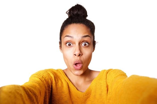 Giovane signora umoristica prendendo selfie