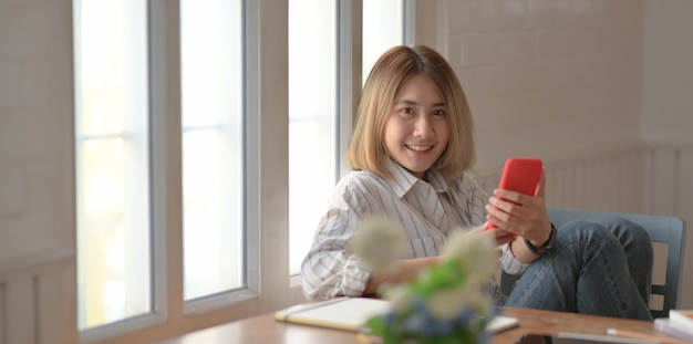Giovane smartphone femminile della tenuta del progettista e sorridere mentre sedendosi sulla sedia