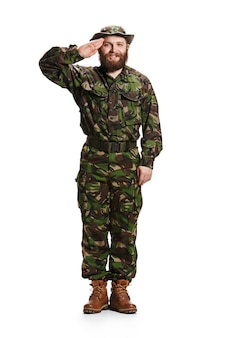 Giovane soldato dell'esercito che indossa l'uniforme del camuffamento in piedi e salutando isolato su sfondo bianco per studio a figura intera. giovane modello caucasico. militare, soldato, concetto dell'esercito. concetti professionali