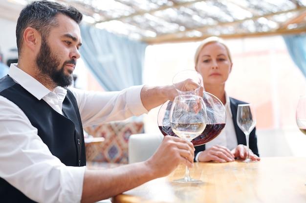 Giovane sommelier o barista maschio barbuto che versa cabernet rosso nel bicchiere di vino prima della degustazione